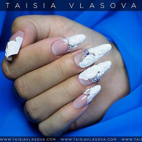 Белый дизайн ногтей с рельефными вензелями, стразами и бульонками